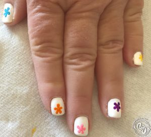 I began by painting a different color, whole flower on each finger; This was to guarantee that each color had at least one whole flower.